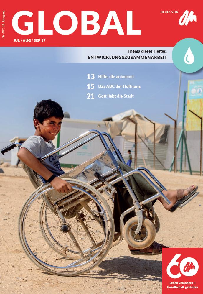 Titel der Global Nr. 407. Junge in einem Flüchtlingslager im Nahen Osten fährt freudig mit einem Rollstuhl.