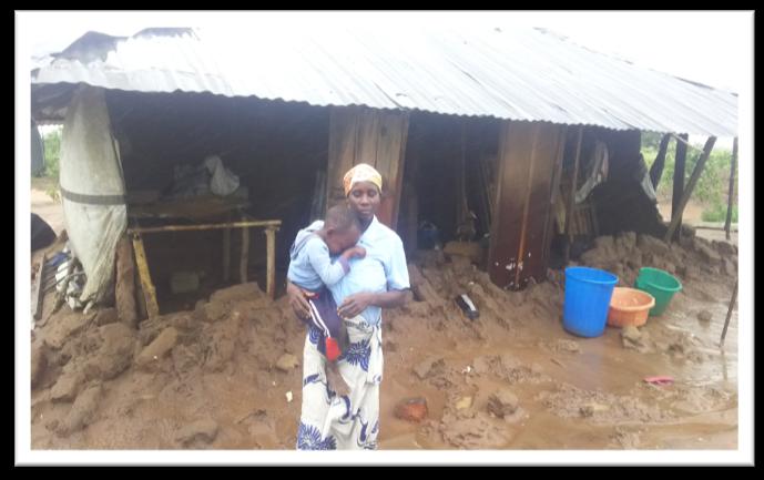 Frau mit Kind vor zerstörtem Haus in Mosambik