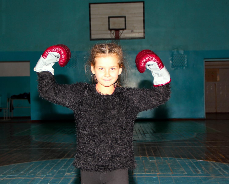 Ein Mädchen posiert mit Boxhandschuhe