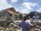 Frau begutachtet die Schäden, die der Hurrikan angerichtet hat