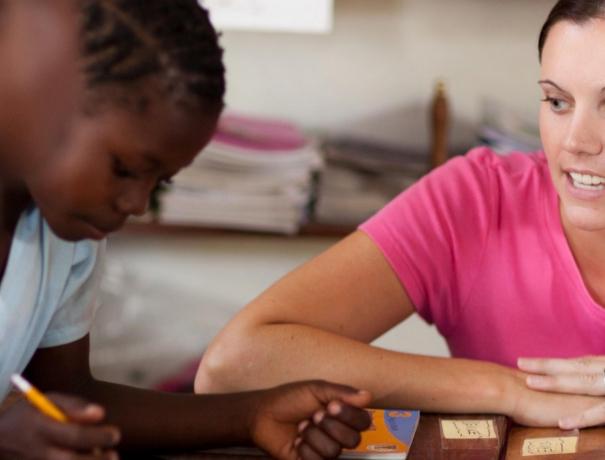 Junge Frau hilft Kindern bei Schularbeiten