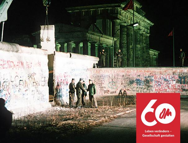 Ein Kran hebt ein Stück der Berliner Mauer weg und Grenzsoldaten begrüßen sich