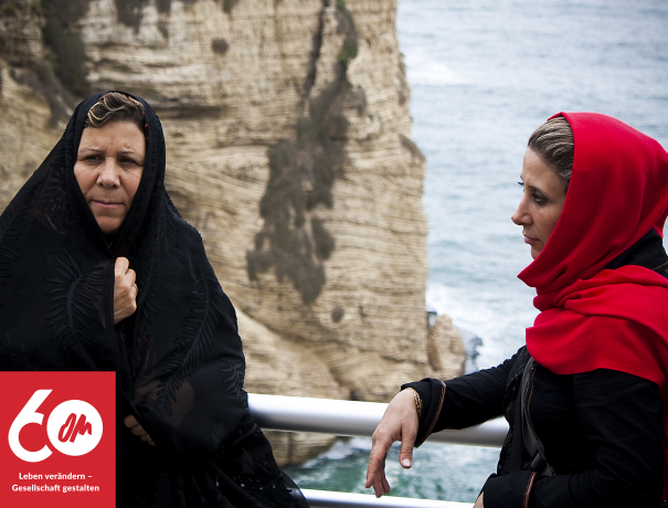 Zwei Iranische Frauen am Meer mit einem Felsen im Hintergrund