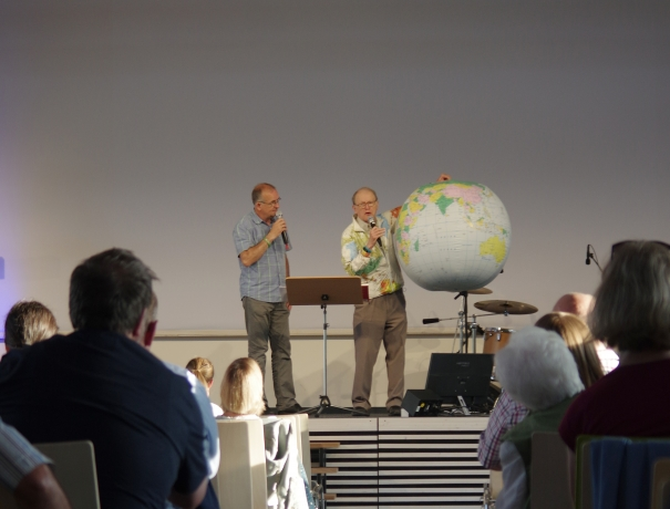 George Verwer predigt in Wetzlar und hält dabei eine aufblasbare Weltkugel in der Hand
