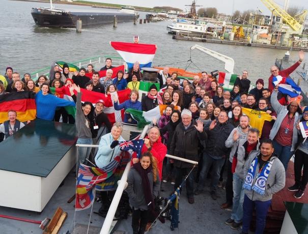 Die Mitarbeiter von OM-Riverboats stehen am Heck des Schiffs und halten ihre Landesflaggen in der Hand.