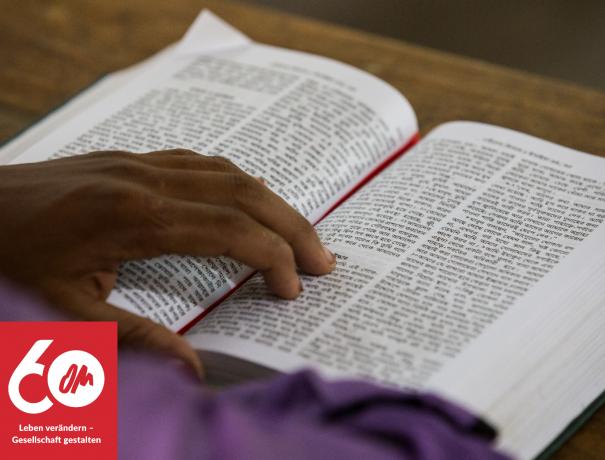 aufgeschlagene bengalische Bibel, mit der Hand des Lesers