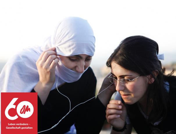 Zwei drusische Mädchen hören etwas von einem MP3-Player