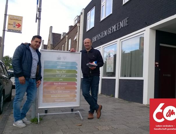 Ein Mitarbeiter und ein Flüchtling stehen neben einem Schild, das für das Begegnungscafé einläd