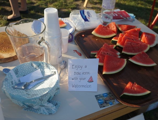 Wassermelonenstücke auf einem Tisch mit Schild auf dem steht Enjoy a biblevers with your watermelon
