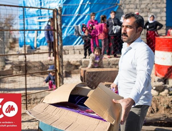 Mann in einem Flüchtlingslager im Irak trägt eine Kiste mit Hilfsgütern