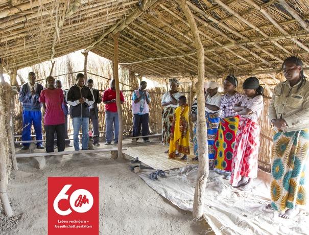 Gemeindemitglieder einer neugegründeten Gemeinde in Chisopi, Malawi stehen zum Gebet in ihrem Gemeinderaum, einer Holzhütte.