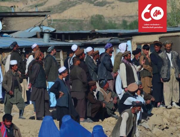 Afgahnen haben sich vor Wellblechhütten versammelt