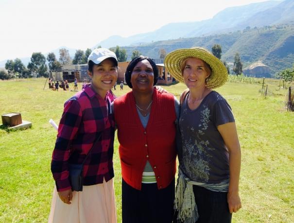 Drei Frauen (Zwei Teilnehmer des MDT und eine Frau aus Lesotho) stehen vor dem Dorf