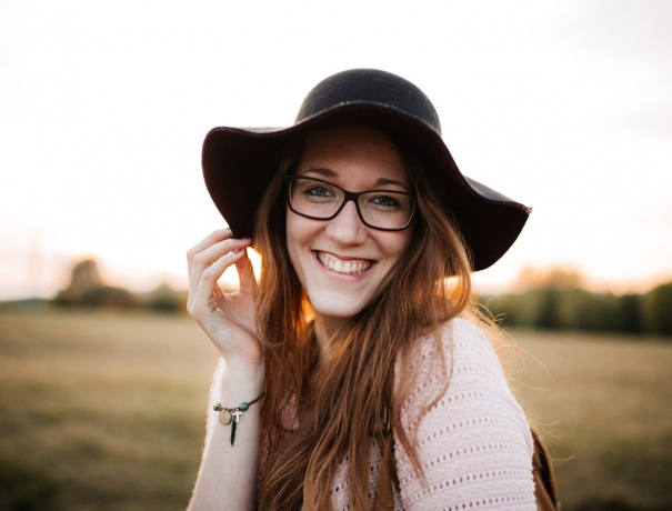 Milena mit einem Hut und einem Lächeln im Sonnenuntergang