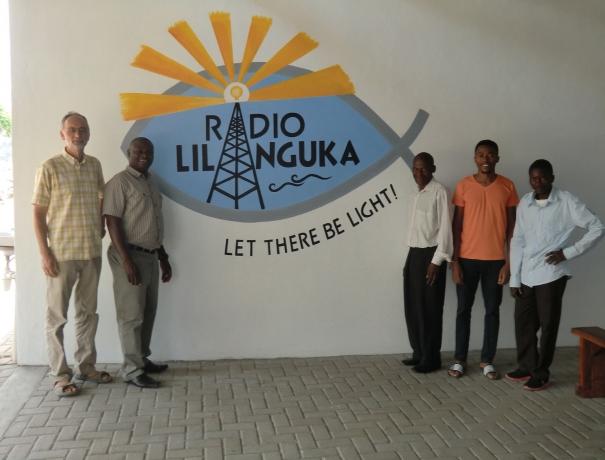 """Mitarbeiter der Radiostation """"Radio Lilanguka"""" stehen vor dem Sendegebäude und freuen sich über den Start."""
