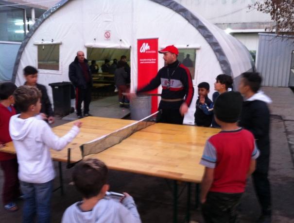 OM-Mitarbeiter bringt im OM-Zelt Flüchtlingskinder Tischtennisspielen bei