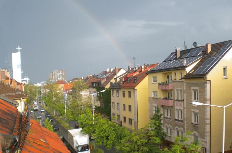 Regenbogen über den Dächern einer Stadt. Links im Bild ist ein Kirchturm mit Kreuz