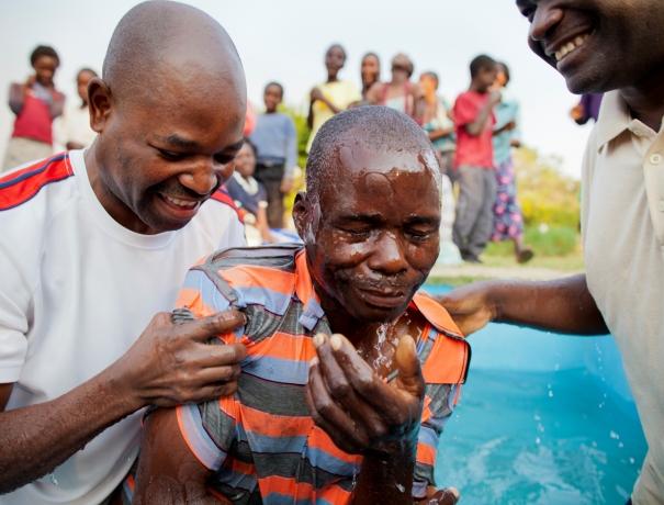 Zwei Gemeindeleiter taufen einen Christen in Afrika