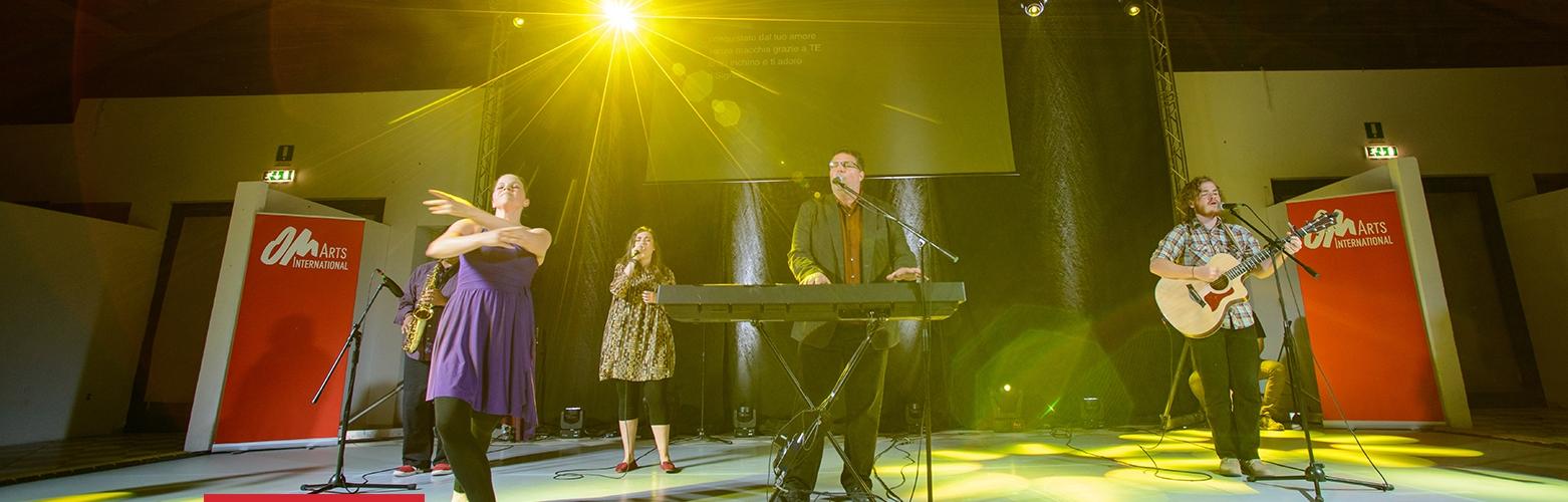 Sänger Bill Drake bei einem Auftritt am E-Piano. Im Hintergrund ein Gitarrist, eine Sängerin und ein Saxophonist, der jedoch von einer Tänzerin im Vordergrund verdeckt ist.