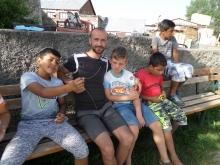 OM-Mitarbeiter mit vier Roma-Jungs auf einer Bank vor einer Mauer