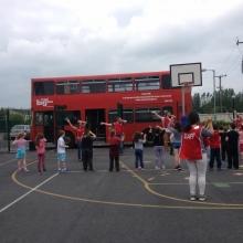 """Während eines Einsatzes mit dem """"Big Red Bus"""" machen Mitarbeiter ein Spiel mit Kindern"""