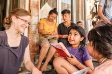 Zwei Mitarbeiterinnen lesen Kindern biblische Geschichten vor