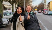 Zwei junge Frauen heben den Daumen und lachen