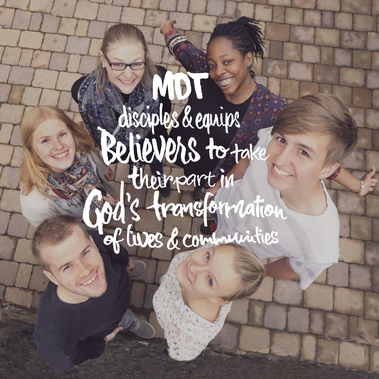 Die Teilnehmer des Jüngerschaftstrainings MDT, darauf die Vision in englisch: disciples & equips Belivers to take their part in God's transformation of lives & communities