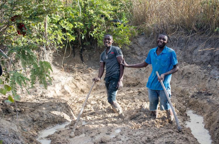 Mosambikilainen John valmistelee maata tiilien tekoa varten yhdessä ystävänsä kanssa.
