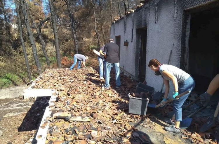 Church members cleaning a house collapsed due the wildfires
