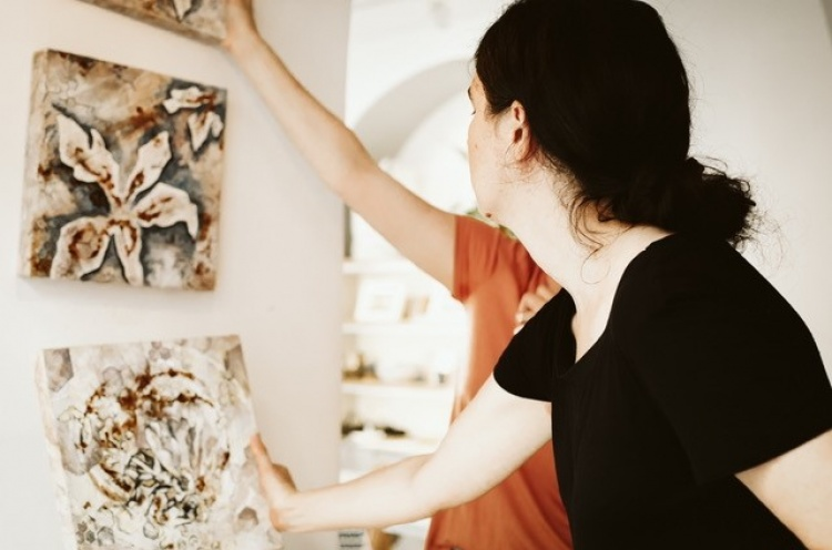 Female artist reaches for artwork on the wall to adjust position